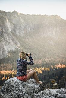 Woman sitting on boulder looking out through binoculars, Yosemite National Park, California, USA - CUF07881