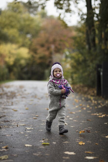 Young girl wearing knitted suit, playing outdoors in autumn - CUF07920