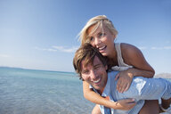 Couple playing piggyback ride by sea - CUF07941