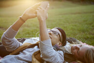 Couple on picnic blanket in park sharing earphone music - ISF01693