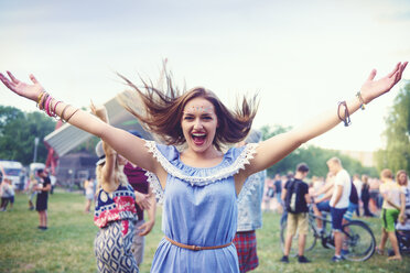 Young boho woman dancing and jumping for joy at festival - ISF01762