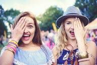 Portrait of two young female friends covering an eye at festival - ISF01765