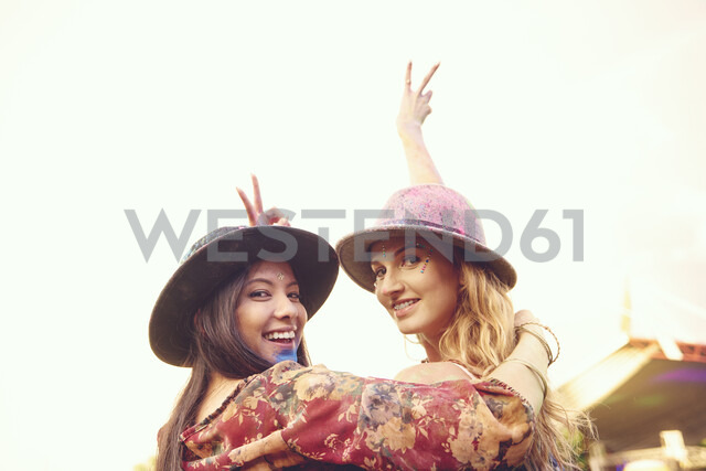 Portrait of two young female friends making peace sign at festival - ISF01771