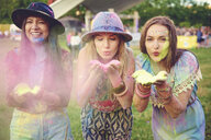 Three young women blowing coloured chalk powder at festival - ISF01777