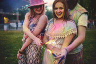 Portrait of two young women and covered in coloured chalk powder at festival - ISF01786