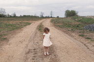 Portrait of shy girl standing on rural dirt track - ISF01819