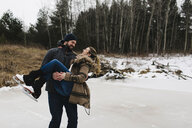 Man skating with woman in his arms, Whitby, Ontario, Canada - ISF01837