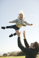Female toddler thrown mid air by father against blue sky - ISF01861