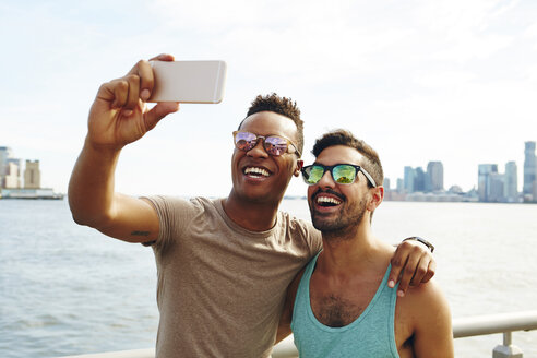 Two young men taking smartphone selfie on waterfront, New York, USA - ISF01945