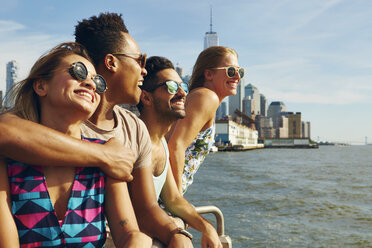 Four adult friends looking out from river waterfront, New York, USA - ISF01966