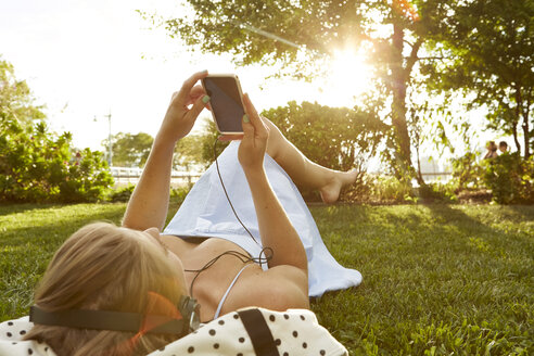 Young woman lying in sunlit park choosing smartphone music - ISF01969