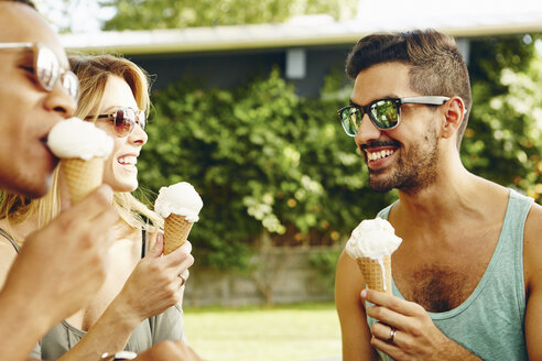 Male and female friends eating ice cream cones in park - ISF02041