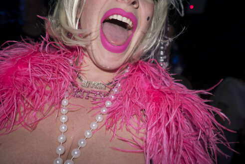 Mid adult woman in party clothes, with pink feather boa and pink lipstick, mid section - ISF02065