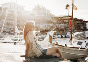 Woman sitting by boats in marina, Es Castell, Menorca, Spain - CUF08225