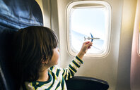 Boy playing with toy airplane at airplane window - CUF08282