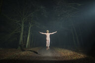 Nude man jumping in woods at night, rear view, Breda, Noord-Brabant, Netherlands - CUF08342