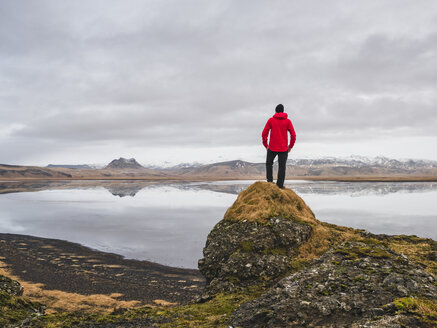 Man standing on rock, looking at view, Dyrholaos, Iceland - CUF08357