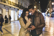 Couple in city, at night, looking at smartphone, Lisbon, Portugal - CUF08366