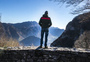 Man standing on wall, looking at mountain view, rear view, Italy - CUF08369