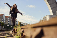 Young woman balancing on train track, low angle view, Bristol, UK - CUF08381