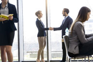 Businesswoman and man shaking hands by office window - CUF08693