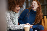 Friends at coffee shop using mobile phone laughing - CUF08765