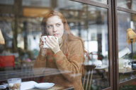 View through window of woman in coffee shop holding cup - CUF08771