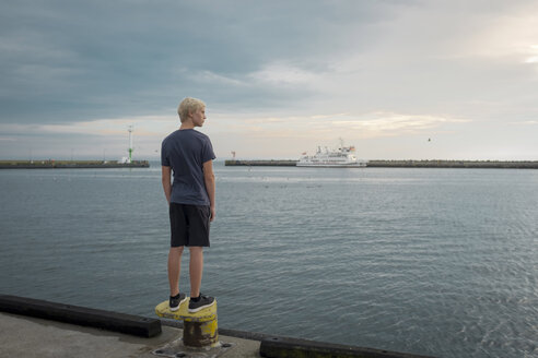 Poland, Gdansk Bay, teenage boy standing on quay looking at distance - HAMF00268