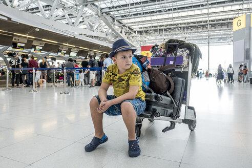Thailand, Bangkok, portrait of boy waiting on baggage cart at airport - MMI00057