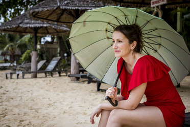Thailand, Koh Phangan, portrait of smiling woman sitting on the beach with umbrella - MMIF00060