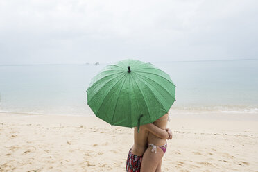 Thailand, boy hugging his mother on the beach under a green umbrella - MMIF00063