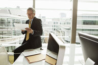 Businessman reading and analysing report, London, UK - CUF08941