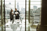 Businessman and businesswoman reading and analysing report, London, UK - CUF08983