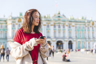 Russia, St. Petersburg, young woman using smartphone in the city - WPEF00252