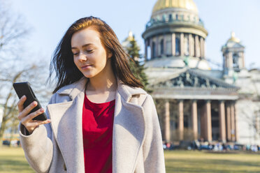 Russia, St. Petersburg, young woman using smartphone in the city - WPEF00255