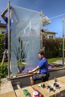 Germany, Glaziers attaching glass pane - HAMF00293