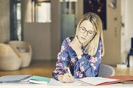 Businesswoman doing paperwork at desk - CUF09211