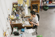 High angle view of male jeweller using blow torch at workbench - CUF09232
