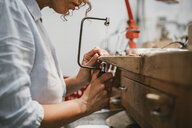 Cropped view of female jeweller using coping saw at workbench - CUF09241