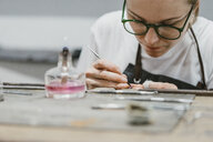 Female jeweller working with miniature hand tool at workbench - CUF09244