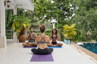 Two women and a man practicing yoga at the poolside - MOMF00413