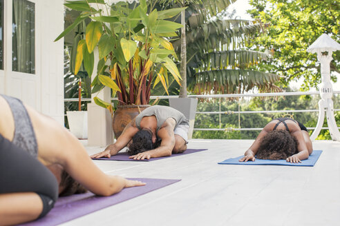 Two women and a man practicing yoga on terrace - MOMF00416