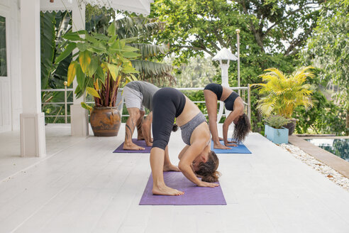 Two women and a man practicing yoga on terrace - MOMF00422