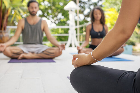 Two women and a man practicing yoga on terrace - MOMF00425