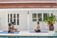 Two women and a man practicing yoga at the poolside - MOMF00428