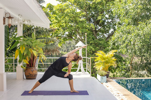 Woman practicing yoga on terrace at the poolside - MOMF00431