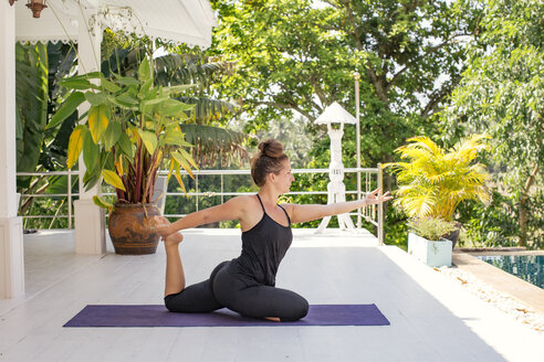 Woman practicing yoga on terrace at the poolside - MOMF00440