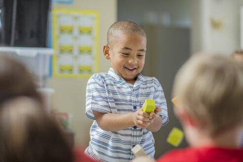 Happy boy playing with other children in kindergarten - ZEF15429