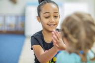 Two happy girls clapping hands in kindergarten - ZEF15444
