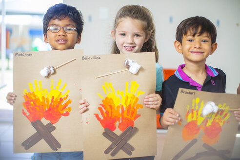 Portrait of smiling children presenting images of fire in kindergarten - ZEF15453